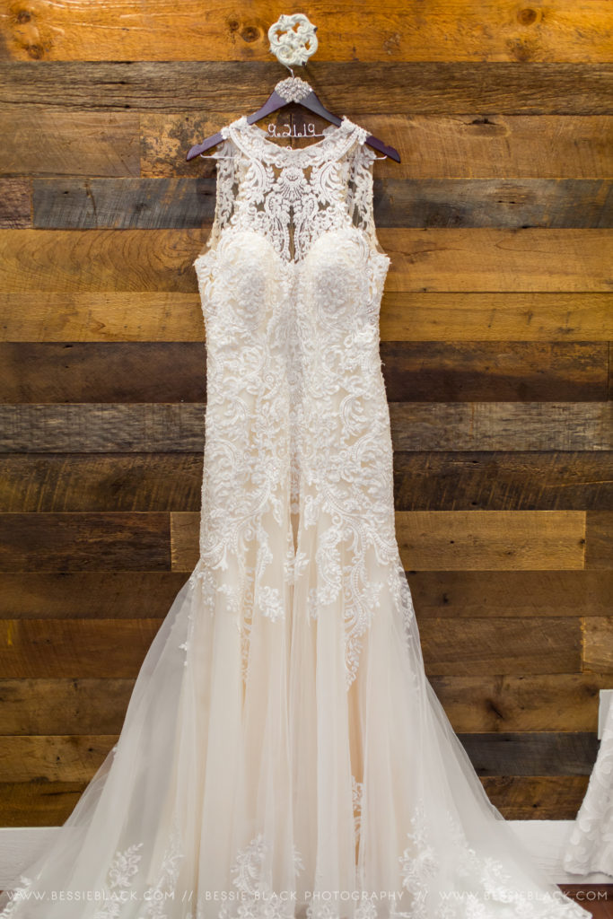 wedding dress hanging against wood